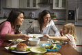 Female gay couple and daughter having dinner in their kitchen Royalty Free Stock Photo