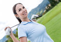 Female golf player at the course holding a club Royalty Free Stock Image