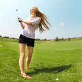 Female golf player at the course practicing to hit ball Stock Images