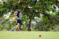 Female golfer hits golf ball Royalty Free Stock Photo