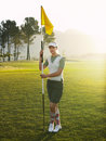 Female golfer holding flag on golf course full length of young Stock Photos