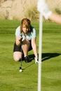 Female Golfer Lining Her Putt Royalty Free Stock Photo