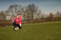 Female golfer lining up a putt kneeling on the green looking at the hole to check the grass and any camber from slope Stock Photos