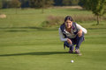 Female golfer lining up a putt kneeling on the green looking at the hole to check the grass and any camber from slope Royalty Free Stock Images