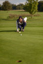 Female golfer lining up a putt kneeling on the green looking at the hole to check the grass and any camber from slope Royalty Free Stock Photo