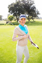 Female golfer standing holding her club smiling at camera Royalty Free Stock Photo