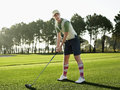 Female golfer teeing off on golf course full length of young Royalty Free Stock Image