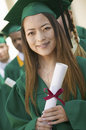 Female graduate holding diploma with friends in background portrait of a the Stock Photography