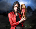 Female grave robber stealing limbs and body parts concept photograph of a in terrifying makeup human Stock Photography