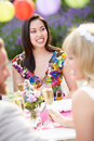 Female guest at wedding reception sitting down looking away from camera smiling Royalty Free Stock Image