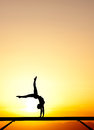 Female gymnast on balance beam in sunset silhouette of Stock Photography
