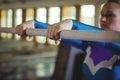 Female gymnast practicing gymnastics on the horizontal bar in the gymnasium Royalty Free Stock Photo