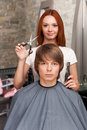 Female hairdresser cutting hair of man client and looking into camera. Royalty Free Stock Photo