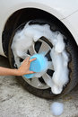 Female hand is cleaning car tire with blue sponge Royalty Free Stock Photo