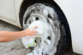 Female hand is cleaning car tire Royalty Free Stock Photo