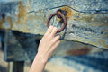 Female hand grabbing rusty chain a young is an old attached to a wooden beam Royalty Free Stock Photos
