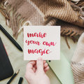 Female hand holding card with handwritten inspirational quote `make your own magic` Royalty Free Stock Photo