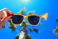 Female hand holding colorful sunglasses against palm tree and blue sunny sky Royalty Free Stock Photo