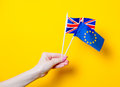Female hand holding EU and Great Britain flags Royalty Free Stock Photo