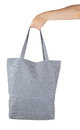 Female hand holding a gray textile shopping bag Royalty Free Stock Photo