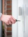 Female hand holding key to insert in door lock Royalty Free Stock Photo