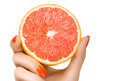 Female hand holding a luscious healthy grapefruit isolated with pretty manicured nails with orange nail varnish in matching color Royalty Free Stock Image