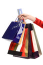 Female hand holding many shopping bags and a credit card of woman with paying with ready for spending isolated on white Royalty Free Stock Image