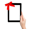 Female hand holding a tablet with isolated screen and a red gift Royalty Free Stock Photos