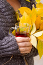 Female hand holding tea and autumn leaves a glass of Stock Photos