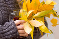 Female hand holding tea and autumn leaves a glass of Royalty Free Stock Photo