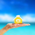 Female hand holding a yellow house on sea background Royalty Free Stock Photo