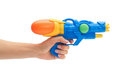 Female hand holds blue squirt gun. Isolated on white background Royalty Free Stock Photo