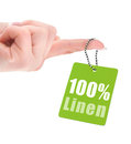 Female hand with hundred percent linen tag over white background Stock Images