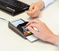 Female hand makes payment via bank terminal in office Stock Photography