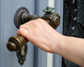 Female hand with old handle bar opening door Royalty Free Stock Photo