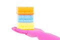 Female hand in pink rubber glove with colorful sponges over whit white background Stock Images