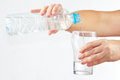 Female hand pour fresh water into a glass from bottle on white background Royalty Free Stock Images