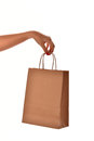 A female hand with red nail hold a paper shopping bag at the stu Royalty Free Stock Photo