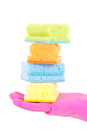 Female hand in rubber glove with colorful sponges over white Stock Photography