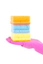 Female hand in rubber glove with colorful sponges over white background Stock Photos