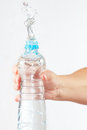 Female hand shaking bottle of water with a splash Royalty Free Stock Photo