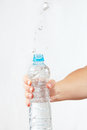 Female hand shaking a small bottle of mineral water with splash Royalty Free Stock Image
