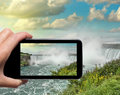 Female hand with smartphone taking a picture of Niagara Falls. T Royalty Free Stock Photo