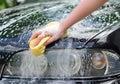 Female hand washing car with yellow sponge Royalty Free Stock Photo