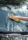 Female hand washing car with yellow sponge Royalty Free Stock Images