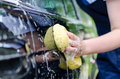 Female hand washing car with yellow sponge Stock Photo
