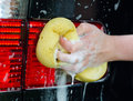Female hand washing car with yellow sponge Stock Photography