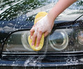 Female hand washing car with yellow sponge Stock Photos