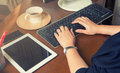 Female hand working computer on working wooden desk with coffee and mobile phone and soft focus, flare sun light, cr Royalty Free Stock Photo