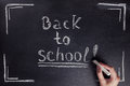 Female hand writes the phrase Back to school with white chalk on black chalkboard. Royalty Free Stock Photo